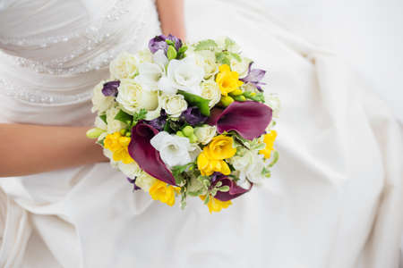 nature photography: Woman in white wedding dress holding wedding flowers