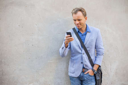 man standing: Man standing by the wall and looking at his telephone Stock Photo