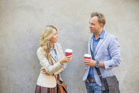 interested: Man and woman standing by the wall and talking Stock Photo