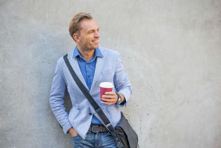 to go cup: Man standing by the wall and smiling Stock Photo