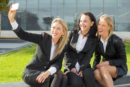 personas mirando: Three women in suits taking a photo