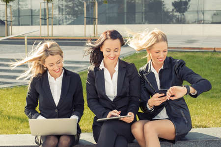 Three business women sitting and using technology