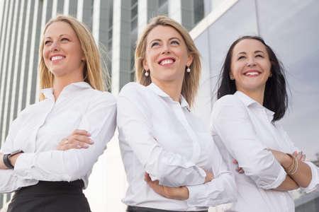 mani incrociate: Donne d'affari in piedi con le mani incrociate