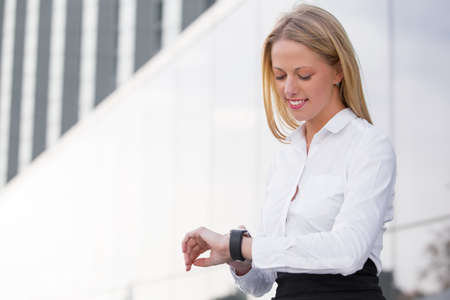 looking at watch: Corporate business woman looking watch and smiling Stock Photo