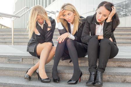 decepción: Tres mujeres de negocios corporativos que se sientan en las escaleras Foto de archivo
