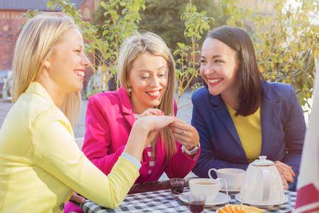 women coffee: Woman showing  friends her ring