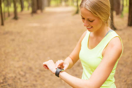 salud y deporte: Woman monitoring her pulse on smartwatch