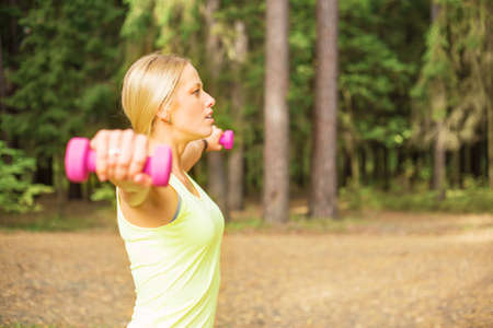 muscular arm: Active woman working out with dumbbells