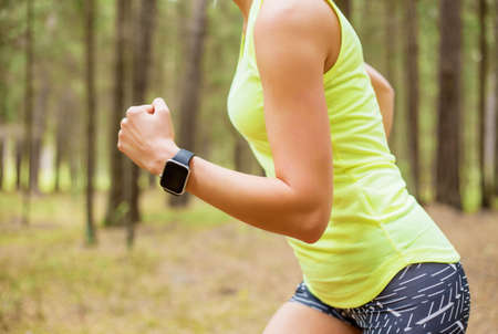 Woman running with smartwatch Stock Photo