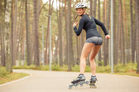 Woman rollerskating and looking back Stock Photo