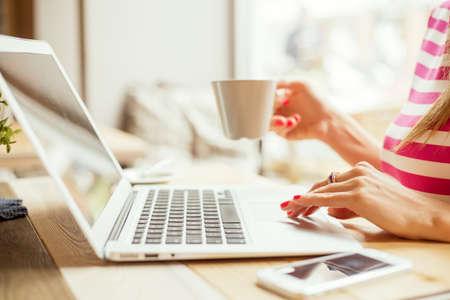 Femme de boire du café et utilisant un ordinateur portable Banque d'images - 46693469