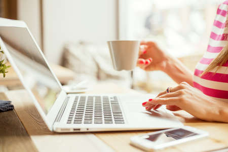 Woman drinking coffee and using laptop Standard-Bild