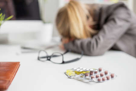 hand holding pills: Woman sleeping on desk after taking pills