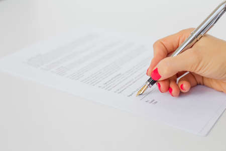 writes: Woman signing papers Stock Photo