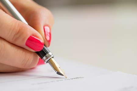 contratos: Mujer firma de contrato Foto de archivo