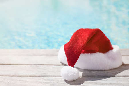 Red Christmas hat sitting by the pool 스톡 콘텐츠