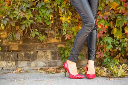 tacones rojos: Mujer de pie junto a la pared