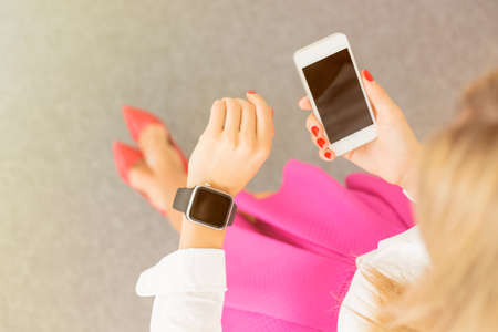 wireless technology: Woman using smartwatch and cellphone Stock Photo