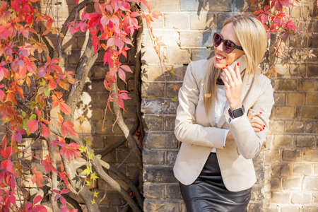 casual woman: Woman on the phone leaning against the wall Stock Photo