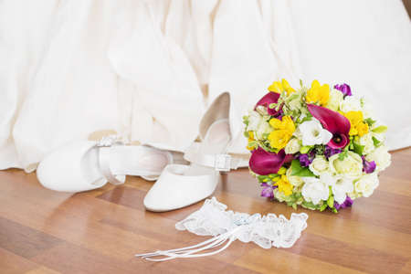 garter: Brides wedding shoes, garter, and flowers sitting on the floor