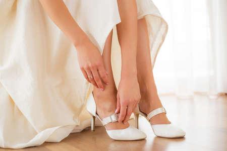 ceremonia: Novia que pone en sus zapatos blancos Foto de archivo