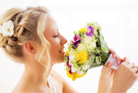 romantic flowers: Bride smelling her wedding flowers Stock Photo