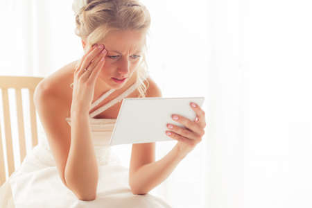 Worried bride looking at tablet Stock Photo