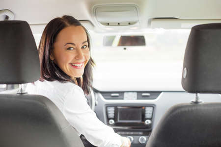 female driver: Woman looking back from drivers seat Stock Photo