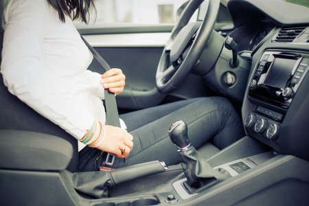 Woman in the car buckling up