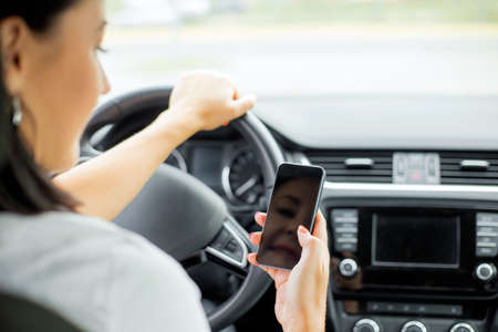 text message: Woman driving and looking at cellphone