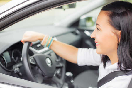 buckled: Buckled up woman driving with one hand on steering wheel Stock Photo