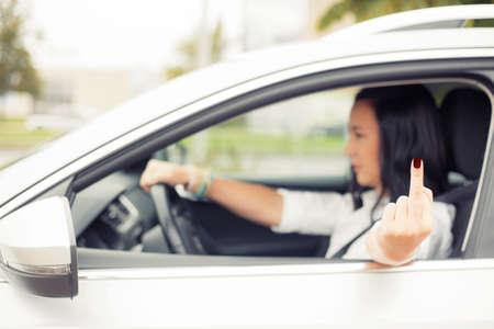 personas enojadas: Mujer que conduce y voltear la gente con el dedo medio Foto de archivo