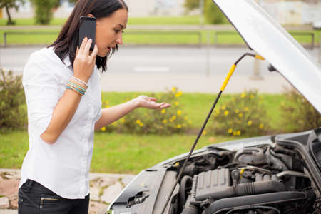 Woman standing next to broken car and talking on the phone