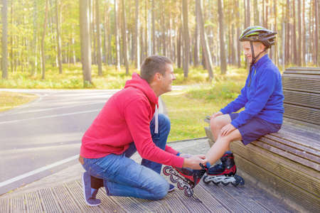 niño en patines: Padre atar hijos patines Foto de archivo