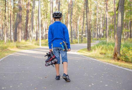 niño en patines: Muchacho con el casco caminando con patines y skate Foto de archivo