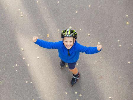 ni�o en patines: Ni�o feliz en patines mostrando las manos en alto Foto de archivo
