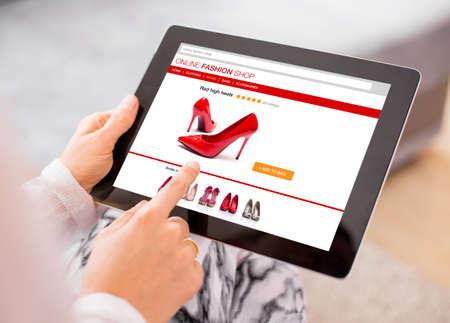 gastos: Mulher que usa a tabuleta digital para fazer compras on-line Imagens