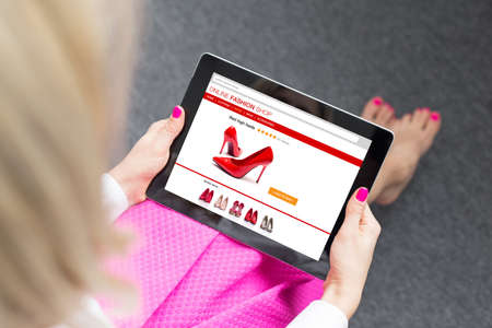 high heel shoes: Woman using tablet to buy shoes online