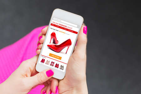 female hand: Female using smartphone to buy shoes online Stock Photo