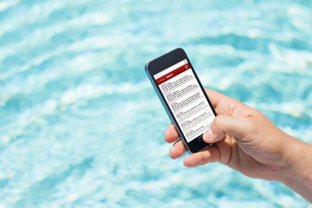 reachable: Man checking email by the pool