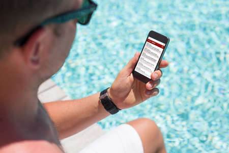 reachable: Man sitting by the pool and checking email on his smartphone Stock Photo