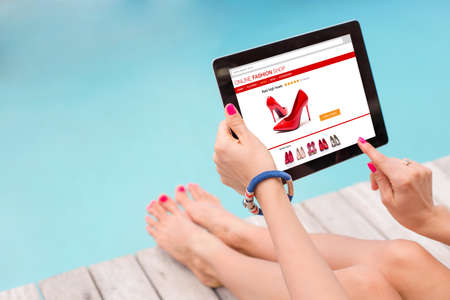 buy online: Female sitting by the pool and using technology to shop online Stock Photo