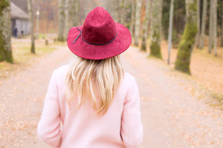 woman alone: Woman in red hat and pink coat walking in park