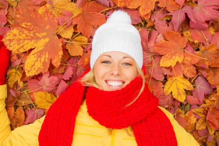 lying on leaves: Happy woman laying in red leafs