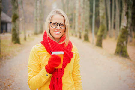 yellow jacket: Girl in yellow jacket and red scarf having coffee