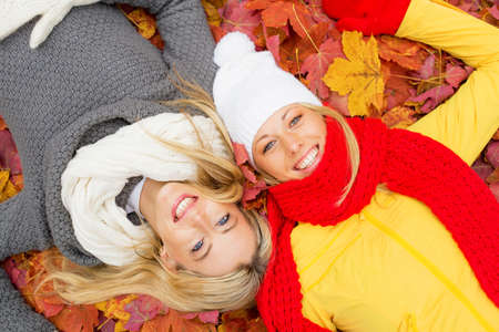 leafs: Two female friends laying in leafs