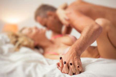 sexo: Hombre y mujer tomados de la mano en la cama