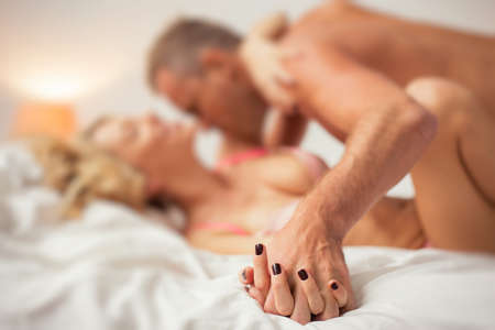 erotic male: Man and woman holding hands in bed