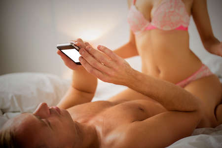 girl boobs: Man looking at his phone while sexy woman is on top of him Stock Photo