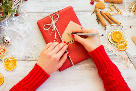 wrapped present: Woman writing on wrapped present Stock Photo